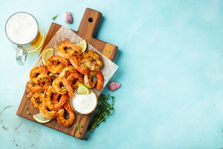Grilled shrimp skewers or langoustines served with lime, garlic and sauce on a light blue concrete background. Seafood and beer. Top view with copy space. Flat lay.