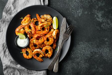Grilled shrimps or prawns served with lime, garlic and white sauce on a dark concrete background. Seafood. Top view with copy space. Flat lay.