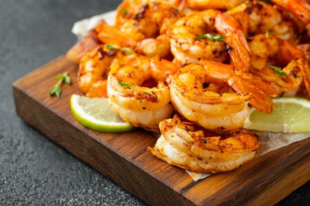 Grilled shrimps or prawns served with lime and garlic on a dark concrete background. Seafood. Stock fotó