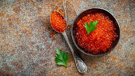 Delicious red caviar in black bowl on a dark concrete background. Top view with copy space. Flat lay.