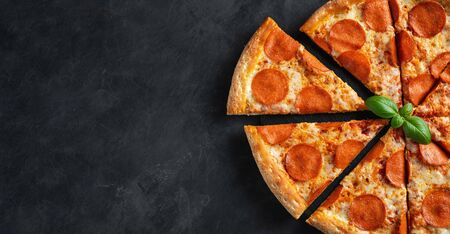 Tasty pepperoni pizza on black concrete background. Top view of hot pepperoni pizza. With copy space for text. Flat lay. Banner. Stock fotó