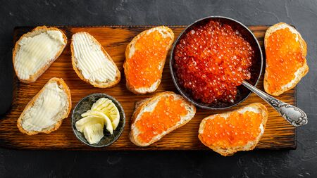 Close-up red caviar in bowl and Sandwiches on wooden cutting board on black background. Top view. Flat lay.