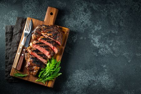 Sliced steak ribeye, grilled with pepper, garlic, salt and thyme served on a wooden cutting board on a dark stone background. Top view with copy space. Flat lay.