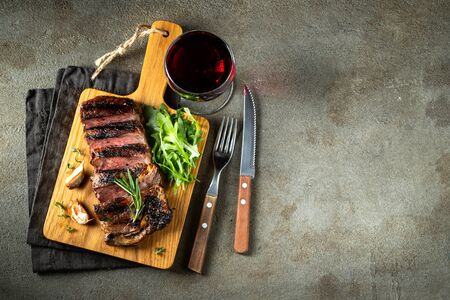 Grilled ribeye beef steak with red wine, herbs and spices. Top view with copy space for  text. Flat lay.