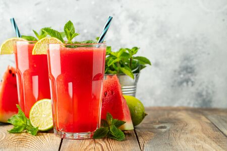 Watermelon slushie with lime and mint, summer refreshing drink in tall glasses on a light background. Sweet cold smoothie with copy space.