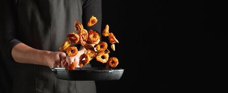 Professional chef prepares shrimps or langoustines with spices. Cooking mediterranean seafood, healthy vegetarian food on a dark background. With copy space for text.
