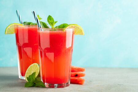 Watermelon slushie with lime and mint, summer refreshing drink in tall glasses on a light blue background. Sweet cold smoothie with copy space. Stock fotó