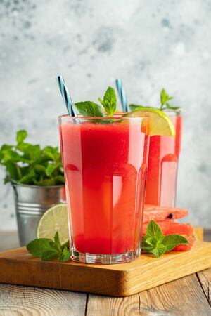 Watermelon slushie with lime and mint, summer refreshing drink in tall glasses on a light background. Sweet cold smoothie.