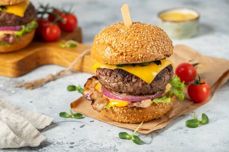 A set of homemade delicious burgers of beef, bacon, cheese, lettuce and tomatoes on a light concrete background. Fat unhealthy food close-up. Stock fotó