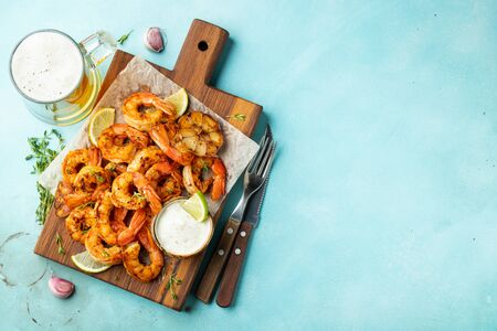 Grilled shrimp skewers or langoustines served with lime, garlic and sauce on a light blue concrete background. Seafood and beer. Top view with copy space. Flat lay Reklamní fotografie