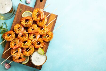 Grilled shrimp skewers or langoustines served with lime, garlic and sauce on a light blue concrete background. Seafood and beer. Top view with copy space. Flat lay Banque d'images