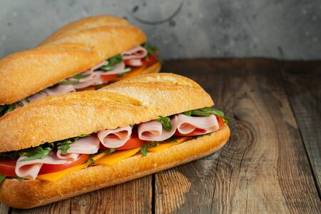 Two Long baguette Sandwiches with arugula, slices of fresh tomatoes, ham and cheese Standard-Bild