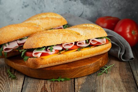 Two Long baguette Sandwiches with arugula, slices of fresh tomatoes, ham and cheese.