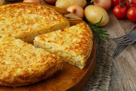 Spanish omelette with potatoes and onion, typical Spanish cuisine. Tortilla espanola. Rustic dark background.