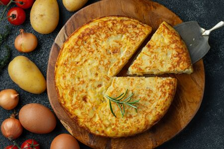 Spanish omelette with potatoes and onion, typical Spanish cuisine. Tortilla espanola. Rustic dark background. Top view.