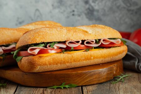 Two Long baguette Sandwiches with arugula, slices of fresh tomatoes, ham and cheese. Stock Photo