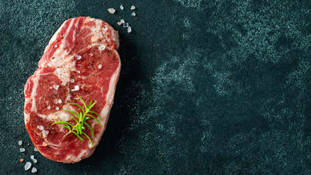 Raw fresh meat Ribeye Steak and seasoning on dark background. Top view with copy space. Flat lay