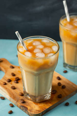 Ice coffee in a tall glass with cream poured over and coffee beans on a light stone background. Cold summer drink with tubes.