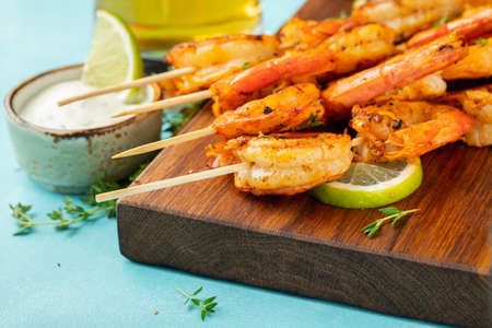 Grilled shrimp skewers or langoustines served with lime, garlic and sauce on a light blue concrete background. Seafood.