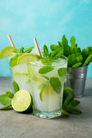 Two homemade lemonade or mojito cocktail with lime, mint and ice cubes in a glass on a light stone table. Fresh summer drink
