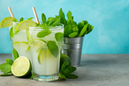 Two homemade lemonade or mojito cocktail with lime, mint and ice cubes in a glass on a light stone table. Fresh summer drink. With copy space Imagens