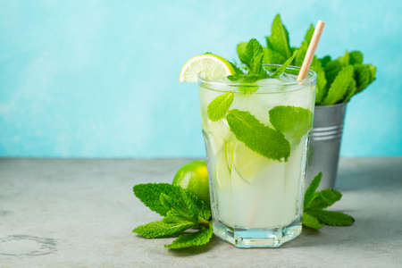 homemade lemonade or mojito cocktail with lime, mint and ice cubes in a glass on a wooden rustic table. Fresh summer drink. with copy space