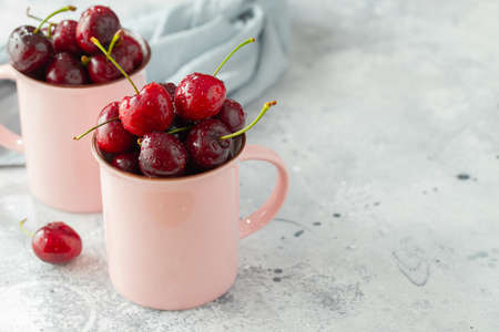 Two pink mugs with fresh ripe cherries. Sweet organic berries on a light concrete background. With copy space. Imagens