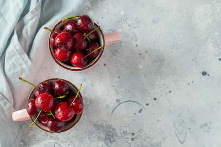 Two pink mugs with fresh ripe cherries. Sweet organic berries on a light concrete background. Top view with copy space.