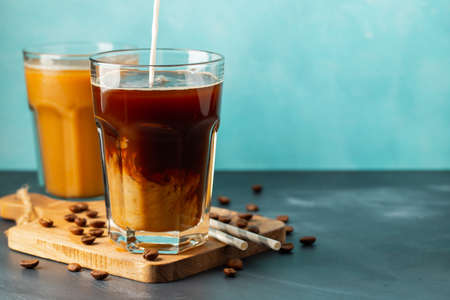 Ice coffee in a tall glass with cream poured over and coffee beans on a light stone background. Cold summer drink with tubes. With copy space.