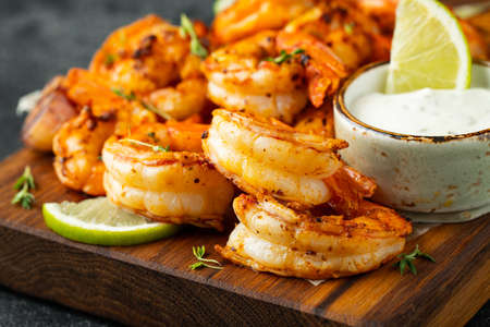 Grilled shrimps or prawns served with lime, garlic and white sauce on a dark concrete background. Seafood.