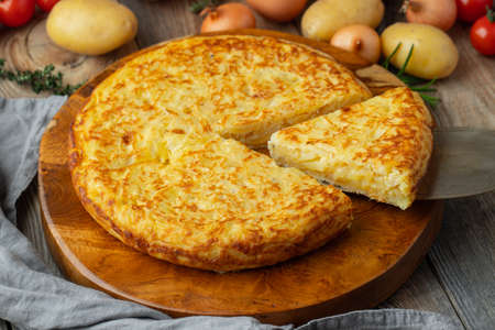Spanish omelette with potatoes and onion, typical Spanish cuisine. Tortilla espanola. Rustic dark background. Imagens