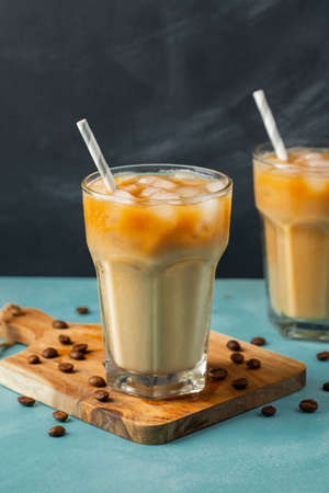 Ice coffee in a tall glass with cream poured over and coffee beans on a light stone background. Cold summer drink with tubes