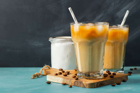 Ice coffee in a tall glass with cream poured over and coffee beans on a light stone background. Cold summer drink with tubes. With copy space