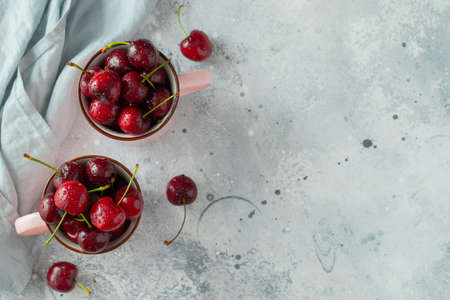 Two pink mugs with fresh ripe cherries. Sweet organic berries on a light concrete background. Top view with copy space Imagens
