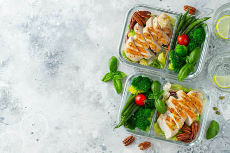 Healthy meal prep containers with green beans, chicken breast and broccoli. A set of food for keto diet in lunchbox on a light concrete background. Top view with copy space