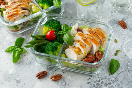 Healthy meal prep containers with green beans, chicken breast and broccoli. A set of food for keto diet in lunchbox on a light concrete background. Top view Imagens