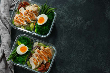 Healthy meal prep containers with green beans, chicken breast and broccoli. A set of food for keto diet in lunchbox on a dark concrete background. Top view with copy space