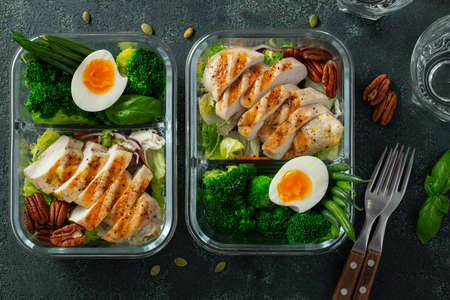 Healthy meal prep containers with green beans, chicken breast and broccoli. A set of food for keto diet in lunchbox on a dark concrete background. Top view