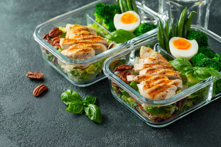 Healthy meal prep containers with green beans, chicken breast and broccoli. A set of food for keto diet in lunchbox on a dark concrete background.