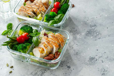 Healthy meal prep containers with green beans, chicken breast and broccoli. A set of food for keto diet in lunchbox on a light concrete background.