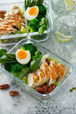 Healthy meal prep containers with green beans, chicken breast and broccoli. A set of food for keto diet in lunchbox on a light concrete background. Top view 版權商用圖片