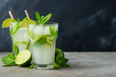 Two homemade lemonade or mojito cocktail with lime, mint and ice cubes in a glass on a dark stone table. Fresh summer drink. With copy space.