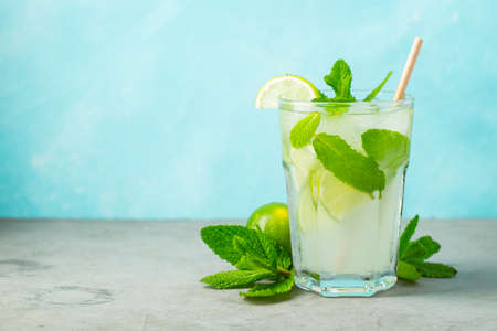 Two homemade lemonade or mojito cocktail with lime, mint and ice cubes in a glass on a light stone table. Fresh summer drink. With copy space.