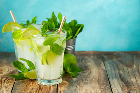 Two homemade lemonade or mojito cocktail with lime, mint and ice cubes in a glass on a wooden rustic table. Fresh summer drink. With copy space.