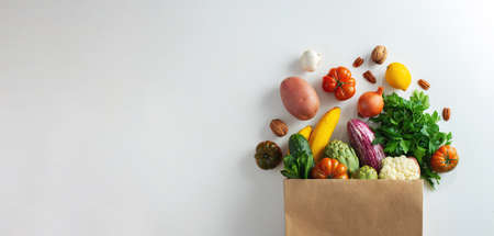Delivery healthy food background. Healthy vegan vegetarian food in paper bag vegetables and fruits on white, copy space, banner. Shopping food supermarket and clean vegan eating concept Фото со стока