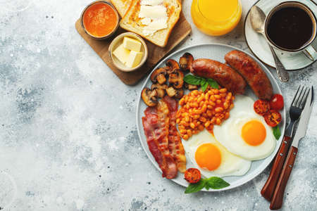 Full English breakfast on a plate with fried eggs, sausages, bacon, beans, toasts and coffee on light stone background. With copy space. Top view