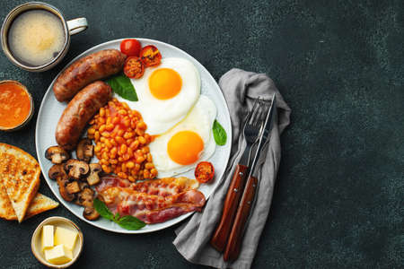 Full English breakfast on a plate with fried eggs, sausages, bacon, beans, toasts and coffee on dark stone background. With copy space. Top view Фото со стока
