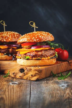 Two delicious homemade burgers of beef, cheese and vegetables on an old wooden table. Fat unhealthy food close-up Фото со стока