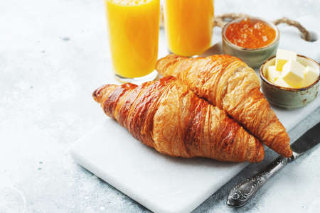 Fresh sweet croissants with butter and orange jam for breakfast. Continental breakfast on a white concrete table. with copy space