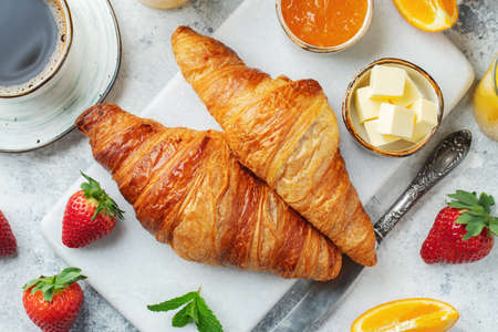 Fresh sweet croissants with butter and orange jam for breakfast. Continental breakfast on a white concrete table. Top view. Flat lay Фото со стока
